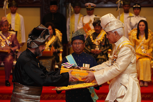 Hajji Baha'uddin 'Adil accepts the royal family medal for his father